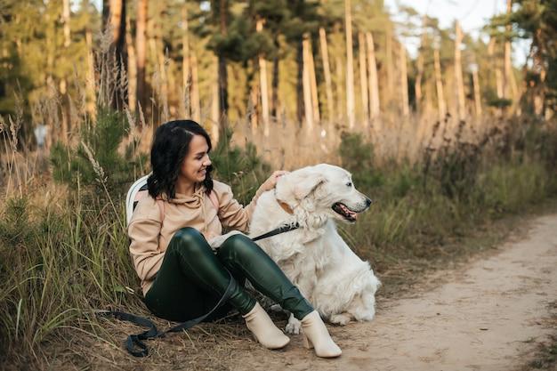 Brunette meisje met witte golden retriever hond op het bospad