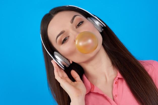 Brunette meisje vormt met kauwgom op blauwe achtergrond.
