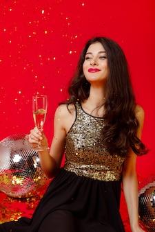 Brunette meisje zit in een zwarte jurk met gouden pailletten en houdt een glas champagne in haar handen