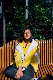Brunette meisje, zittend op een bankje in het centrale deel van de oude stad.