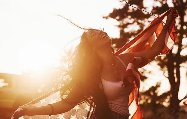 Brunette met amerikaanse vlag in handen heeft een goede tijd en voelt zich buiten op zonnige dag vrij freedom