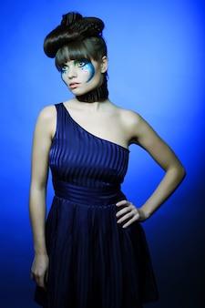 Brunette met creatieve make-up in blauwe jurk