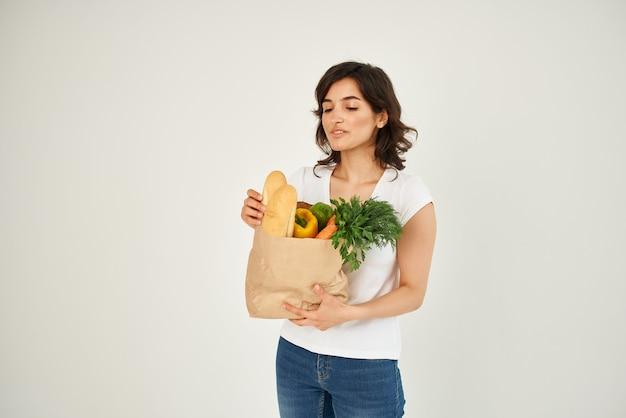 Brunette met een pakket gezonde voeding groenten bezorgen
