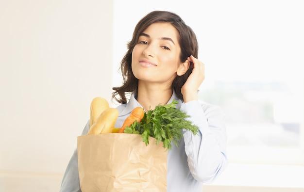 Brunette met een pakket van boodschappen groenten groenten supermarkt winkelen