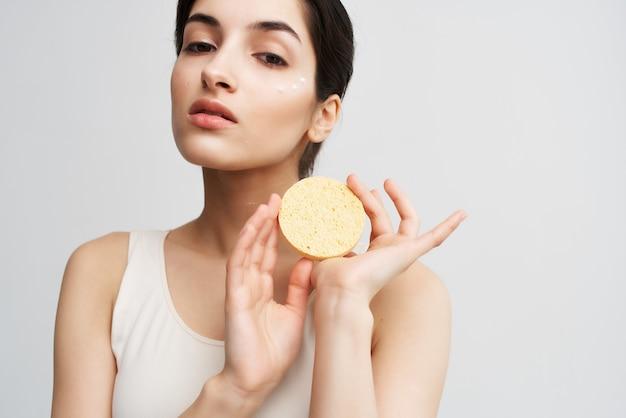 Brunette met een spons in haar handen schone huid gezichtsverzorging cosmetica