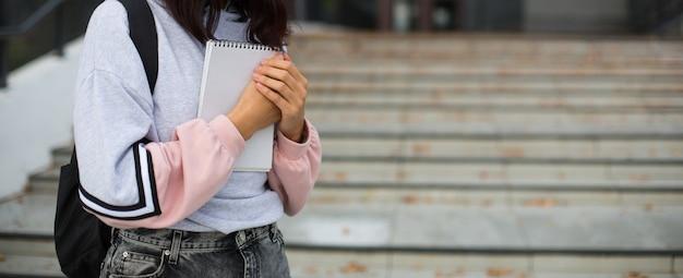 Brunette met een zwarte rugzak en een notitieboekje
