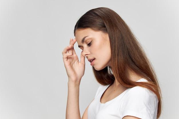 Brunette met gesloten ogen raakt haar gezicht met handen, zijaanzicht van het model