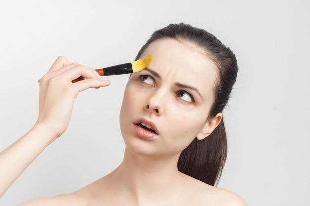 Brunette met getrokken haar, nude schouders, make-up verwijdering huidverzorging.