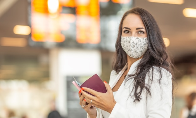 Brunette met gezichtsmasker controleert haar paspoort voordat ze naar het buitenland reist met een luchthaveninformatiepaneel achter haar.