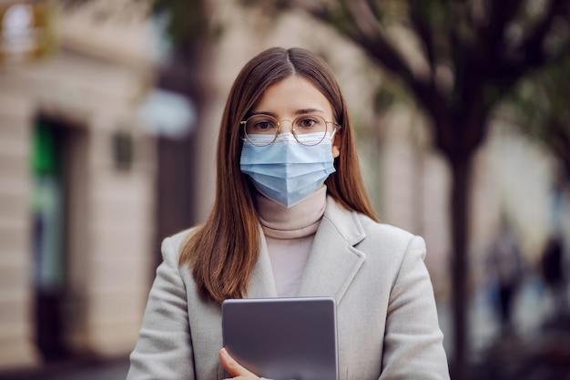 Brunette met gezichtsmasker staande op straat en tablet vast te houden tijdens coronavirus.