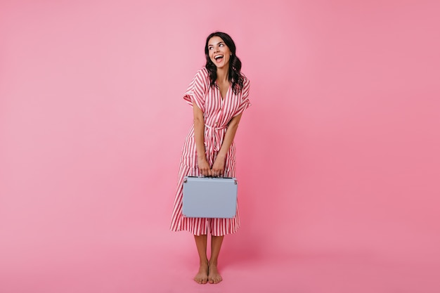 Brunette met golvend haar is schattig poseren in gestreepte midi-jurk. vrouw in stijlvolle outfit kijkt met belangstelling weg.