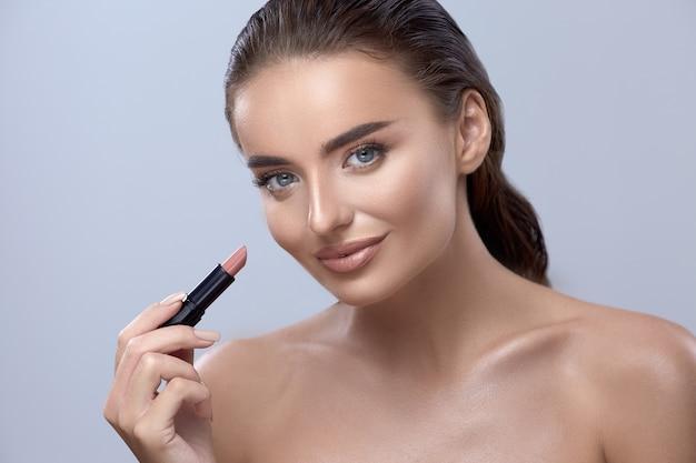 Brunette met lippenstift, smilling vrouw met lippenstift, meisje doet make-up, naakt make-up op gelukkige vrouw