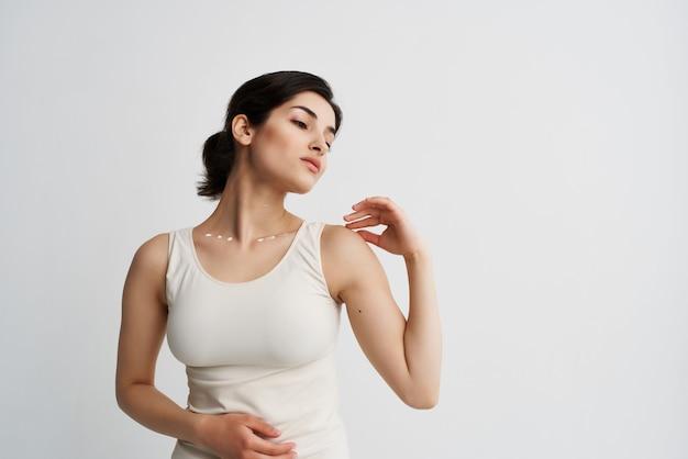 Brunette met lotion in handen cosmetica huidverzorging lichte achtergrond