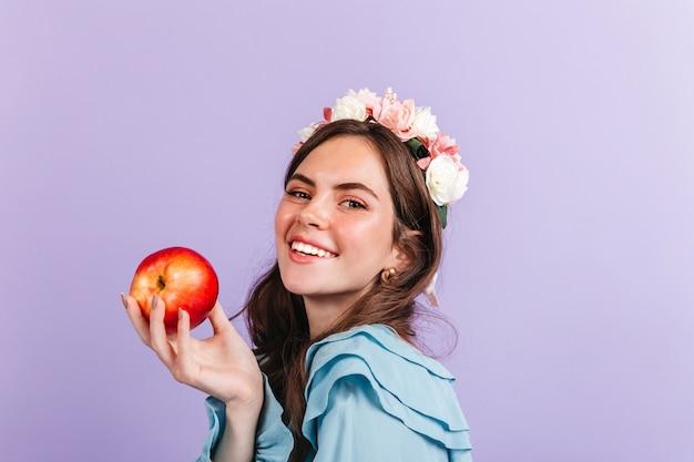 Brunette met rozen in haar haar houdt rode appel vast. close-upportret van meisje in beeld van moderne sneeuwwitje.