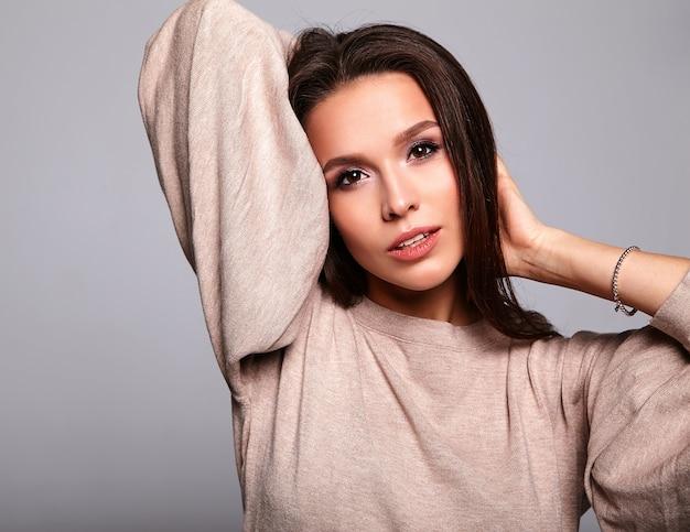 Brunette model in casual beige warme trui kleding op grijs