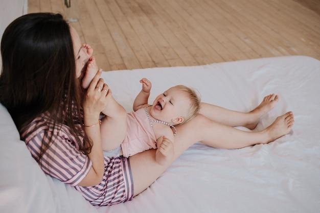 Brunette moeder in gestreepte pyjama speelt met haar dochtertje op het bed in de slaapkamer