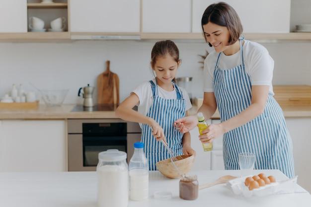 Brunette moeder voegt olie toe aan deeg, dochtertje helpt om gebak te maken, klopt ingrediënten
