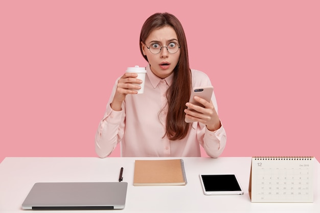 Brunette mooie jonge vrouwelijke blogger leest ontvangen melding op mobiel, heeft uitdrukking verbaasd