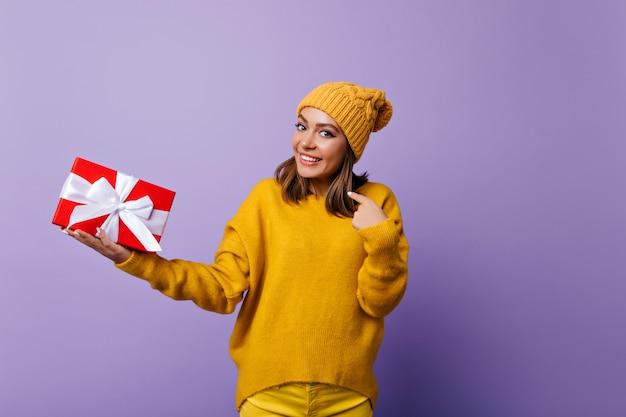 Brunette opgewonden meisje in elegante trui genieten van portraitshoot vóór nieuwjaarsvakantie. extatisch kaukasisch vrouwelijk model met verjaardagscadeau en lachend.
