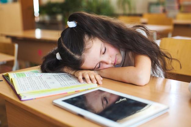 Brunette schoolmeisje leunend op het bureaublad