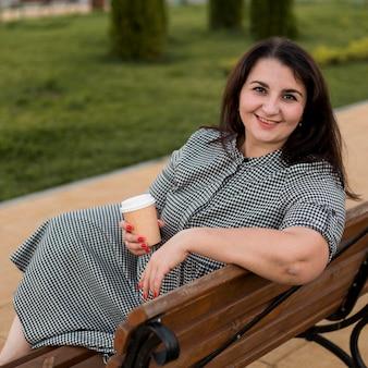 Brunette smileyvrouw met een kopje koffie buiten