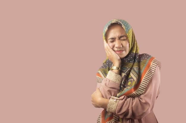 Brunette-spaanse meid die de mond aanraakt met de hand met pijnlijke uitdrukking vanwege kiespijn
