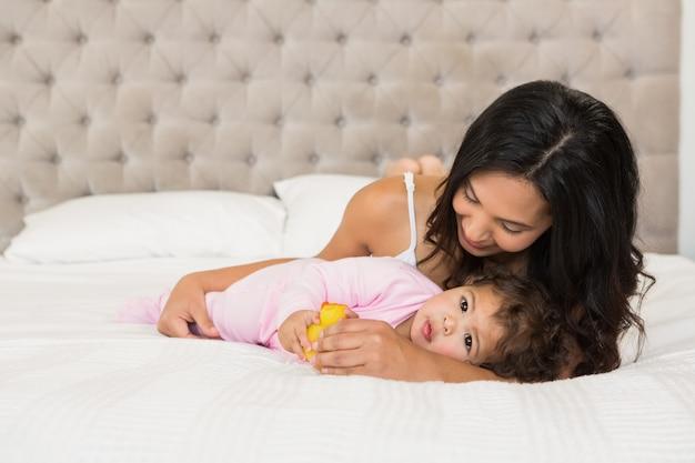 Brunette speelt met haar baby en een eend op het bed