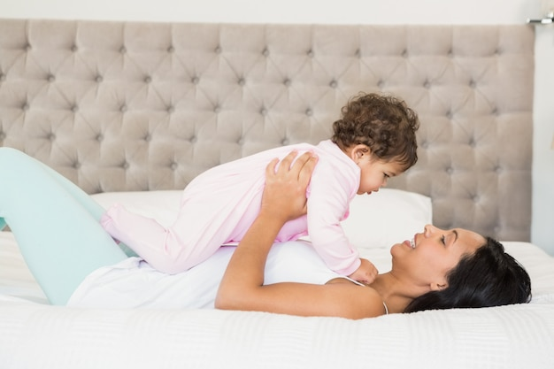 Brunette speelt met haar baby op het bed