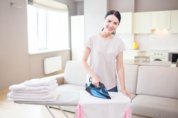 Brunette staat en strijkt witte kleren. ze kijkt op camera en lacht. meisje staat in lichte studio-appartement.