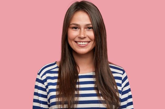 Brunette tevreden meisje met aangename brede glimlach, toont natuurlijke schoonheid, in goed humeur