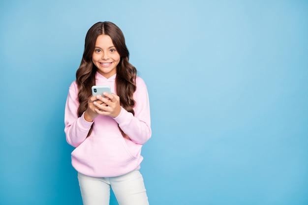 Brunette tiener poseren met haar telefoon tegen de blauwe muur