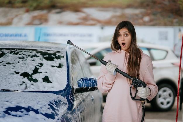 Brunette uit een hogedrukslang brengt een reiniger aan op de auto