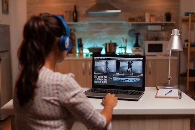 Brunette video-editor werkt 's nachts met beelden op persoonlijke laptop in de keuken thuis home