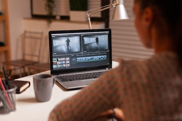 Brunette video-editor werkt 's nachts met beeldmateriaal op persoonlijke laptop in huiskeuken. contentmaker thuis bezig met filmmontage met moderne software voor 's avonds laat bewerken.
