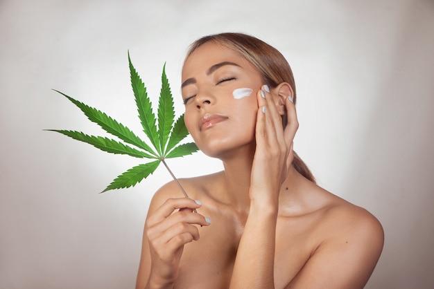 Brunette vrouw cbd gezichtscrème gemaakt van cannabisextract toe te passen. geïsoleerd op een grijze pagina