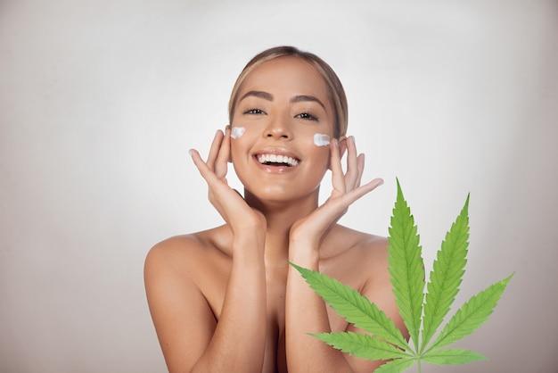 Brunette vrouw cbd gezichtscrème gemaakt van cannabisextract toe te passen. geïsoleerd op grijze achtergrond