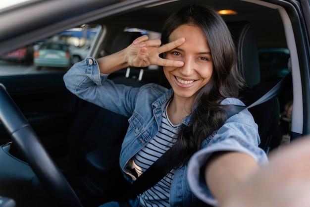 Brunette vrouw die een selfie in haar auto