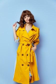 Brunette, vrouw die lacht kijkt ernaar uit met haar met kort haar gele jas