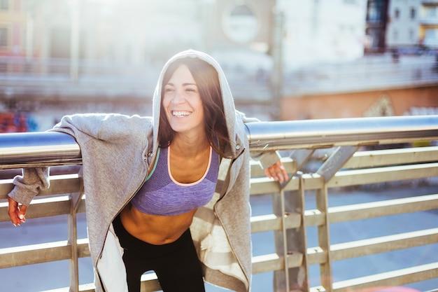 Brunette vrouw draagt sportkleding lachend