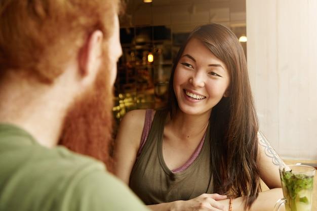 Brunette vrouw en gember man zitten in café