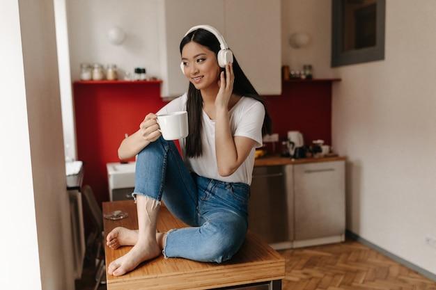 Brunette vrouw gekleed in spijkerbroek en top poseren tegen de achtergrond van de keuken