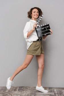Brunette vrouw glimlachend en met zwarte filmklapper, geïsoleerd over grijze muur