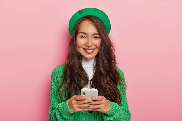 Brunette vrouw houdt moderne mobiele telefoon, stuurt sms-berichten, surft op internet, draagt groene baret en casual trui