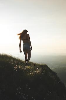 Brunette vrouw in beha en korte broek genietend van het uitzicht vanaf de top van de berg tijdens zonsondergang
