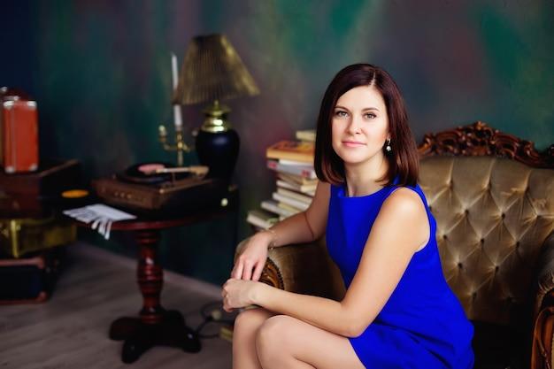 Brunette vrouw in blauwe korte jurk kijkt naar camera zittend op een stoel in vintage kamer