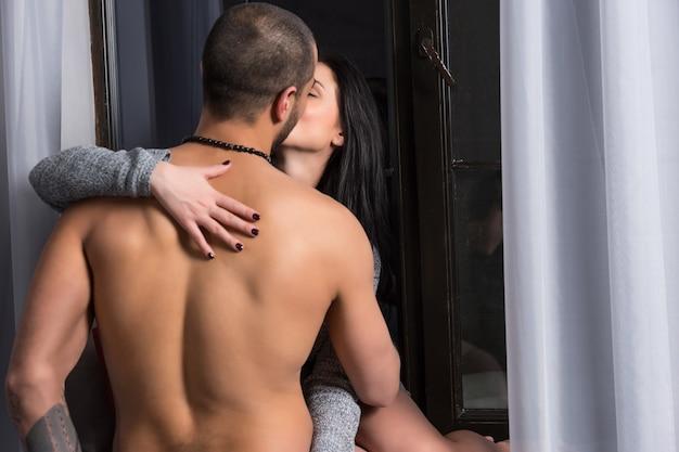 Brunette vrouw in een gebreide jurk zit op de vensterbank en kuste haar man met blote borst en getatoeëerde handen