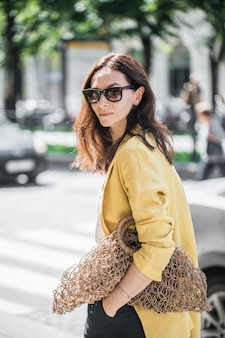 Brunette vrouw in een gele jas en zwarte broek, zonnebril en tas string tas lopen op straat.
