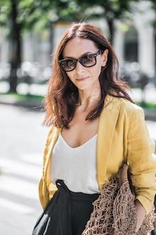 Brunette vrouw in een gele jas en zwarte broek, zonnebril en tas string tas.