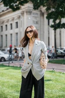 Brunette vrouw in een gestreepte jas en zwarte broek, zonnebril en tas string tas.