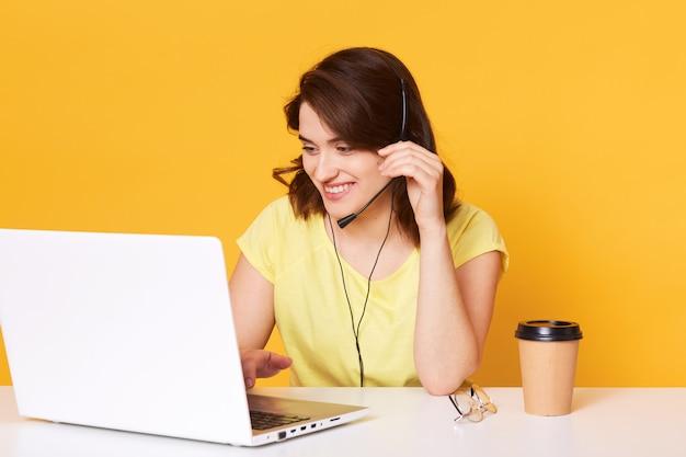 Brunette vrouw in gele casual t-shirt zit op stoel aan witte bureau en werkt op laptop op, heeft een aangenaam gesprek met de klant, houdt de hand op garnituur, werkt online.